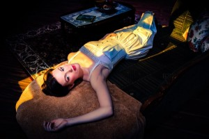 A dark noir style photograph of an actress laying on a fainting couch for the play The Underpants by Steve Martin.