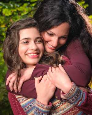 Mother and daughter hug portrait in the fall sun