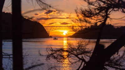 The huge setting sun right under deception pass bridge in Oak Harbor WA