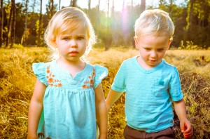 Two toddlers standing in tall grass with sunshine behind them fall color