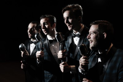 Four 50's doo wop singers with old microphones on the dark stage