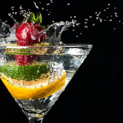 Fruit splashing into a martini glass