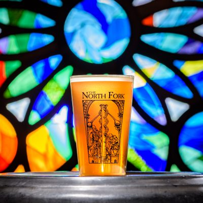 a beer back lit glowing in front of a stained glass window