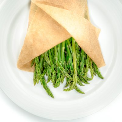 Asparagus on a plate in steaming paper wrap
