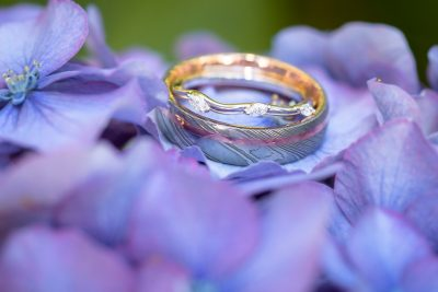 Wedding band and ring bride and groom on purple flower close up